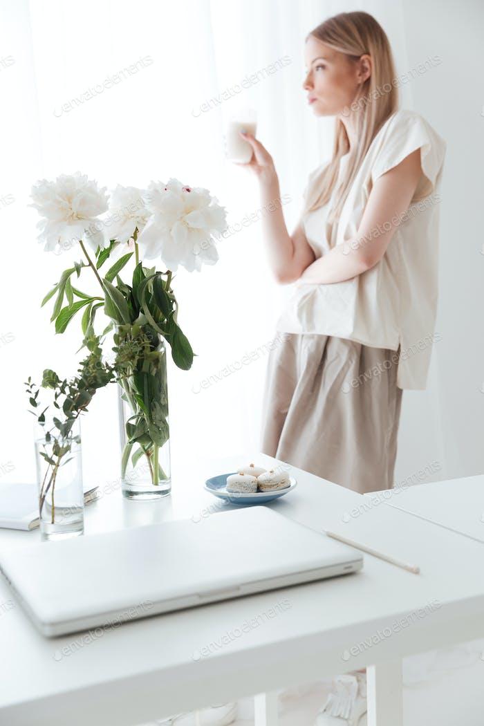 Serious woman standing near window indoors drinking coffee.