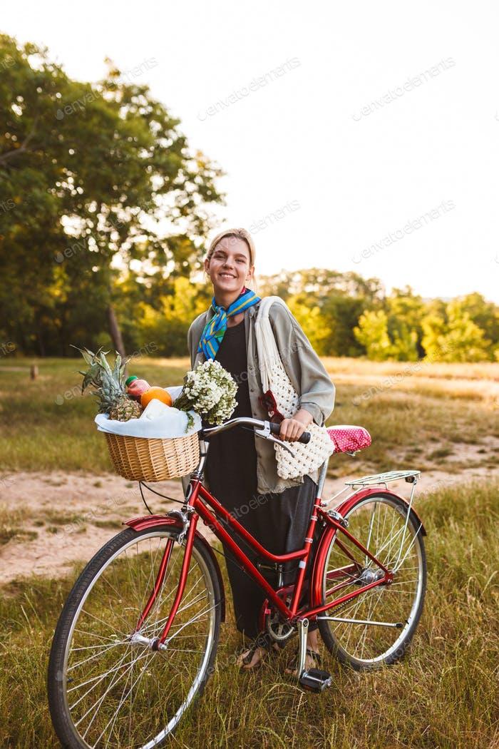 Young smiling girl on red bicycle with wildflowers and fruits in