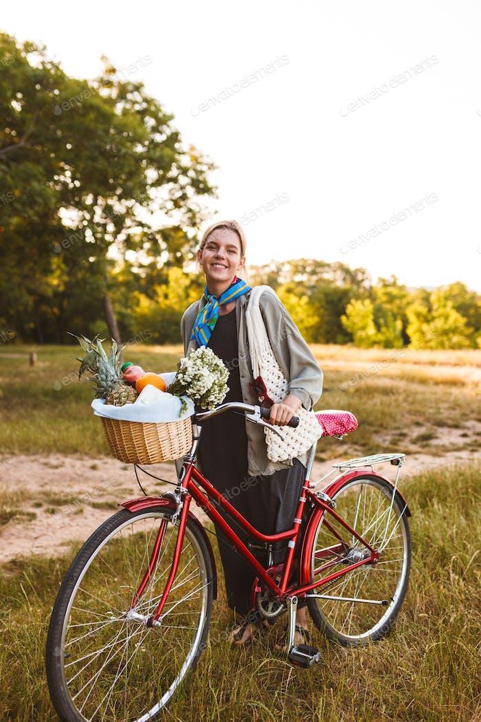 Junges lächelndes Mädchen auf rotem Fahrrad mit Wildblumen und Früchten in