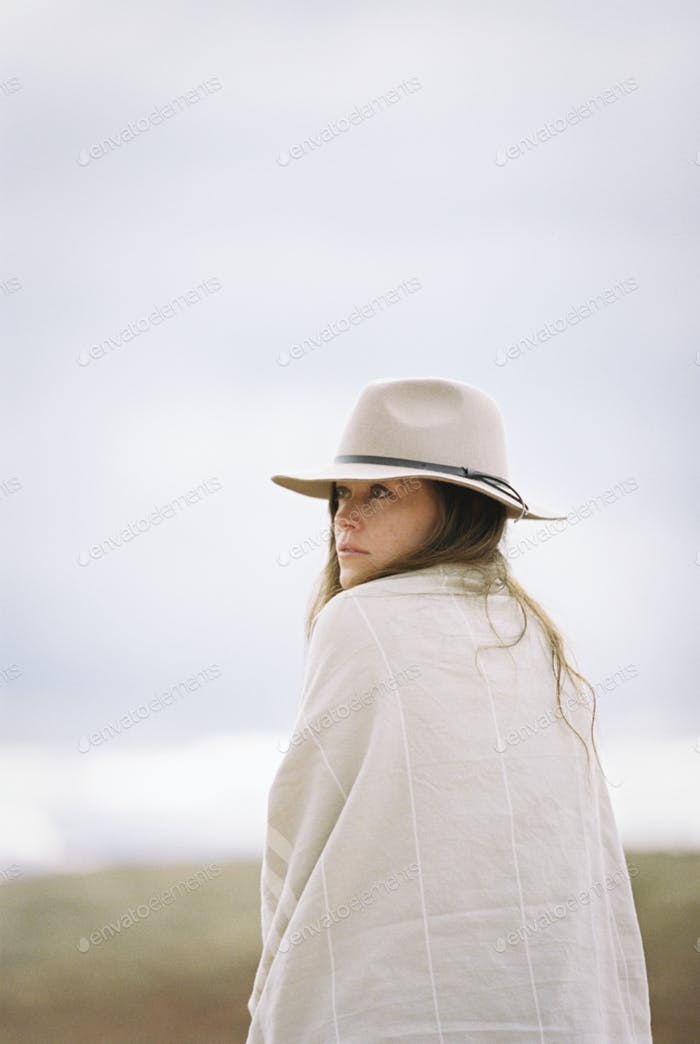 Woman wearing a hat and wrap looking over her shoulder, smiling at the camera.