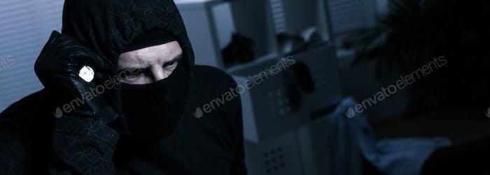 Ladrón enmascarado con linterna