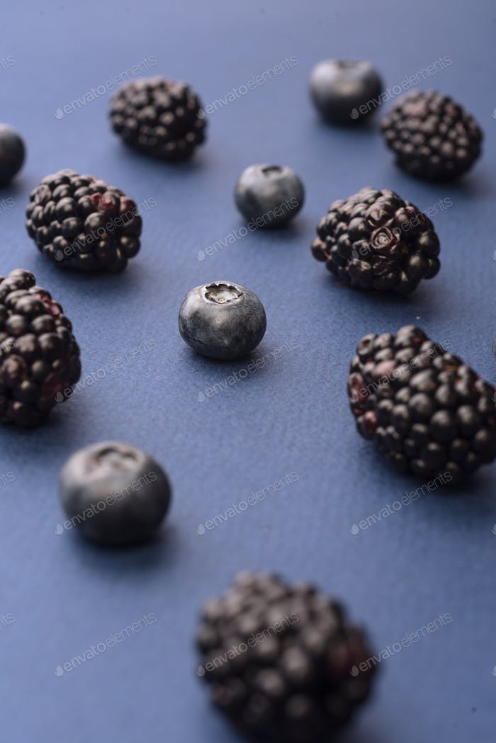 Blueberries and mulberries isolated over blue background table.
