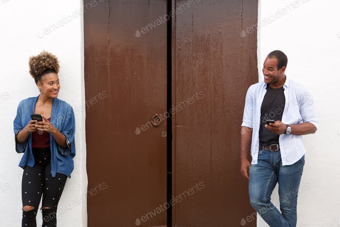 Beautiful couple holding cellphones and standing by door
