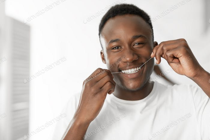 Black Guy Flossing Teeth In Morning Standing In Bathroom Indoors