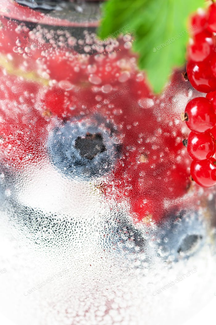 Fresh berries in soda water in a glass close-up on a white backg
