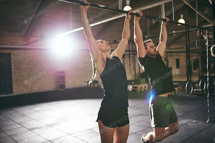 Two young sportsmen doing pull-ups in gym