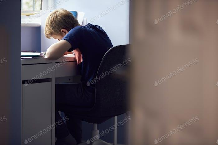 View Through Door Of Boy Sitting At Desk Home-Schooling