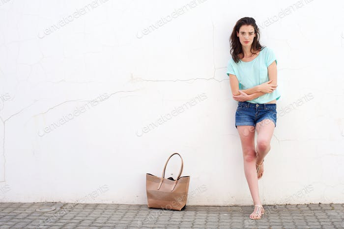 Fashionable young woman with purse leaning against white wall