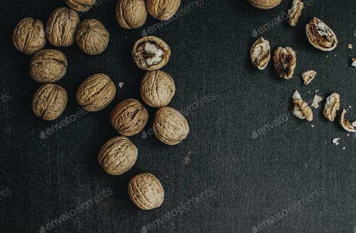 Dried walnuts on a black wooden background