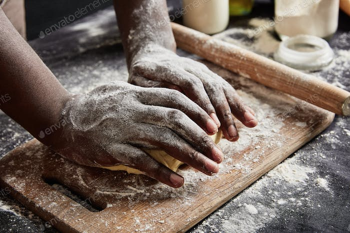 Cropped shot of male`s hands knead dough for preparing roll or pizza, works with rolling pin, uses f