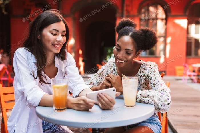 Two beautiful ladies happily using cellphone together with drink