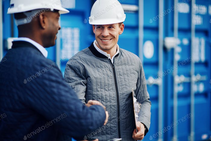 Smiling engineers standing in a shipping yard shaking hands together