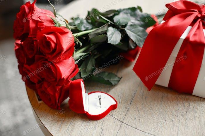 Ehering mit einem Diamanten auf einem Tisch mit Blumen in einem Café