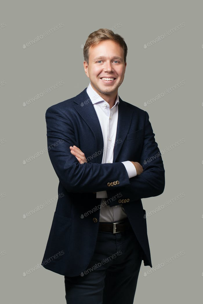 Cheerful businessman with crossed arms isolated on grey