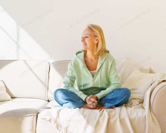 Positive senior woman looking in window and expressing positivity while relaxing on sofa at home