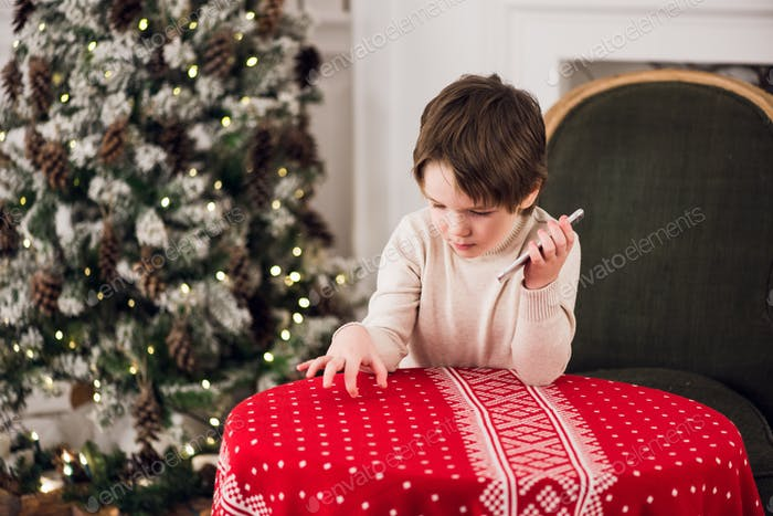 boy calls Santa while sitting on a big green armchair at home over chirstmas tree background