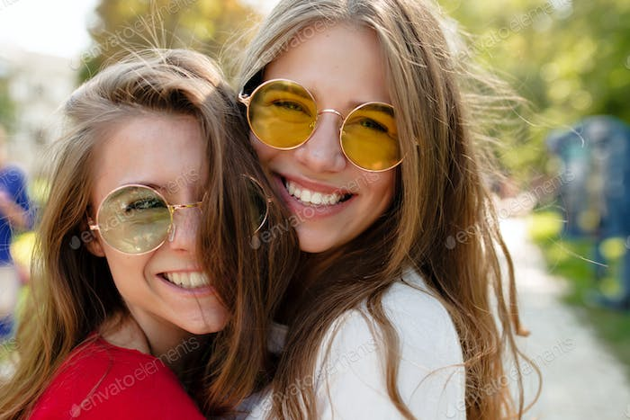 Close up outdoor portrait of two cheerful female best friends in bright glasses