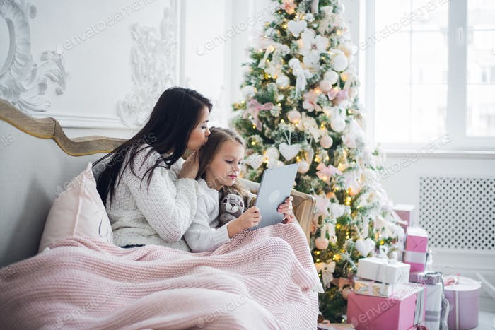 Mother With Daughter On Couch Using Tablet Computer Happy Smiling Young Family Near Decorated New