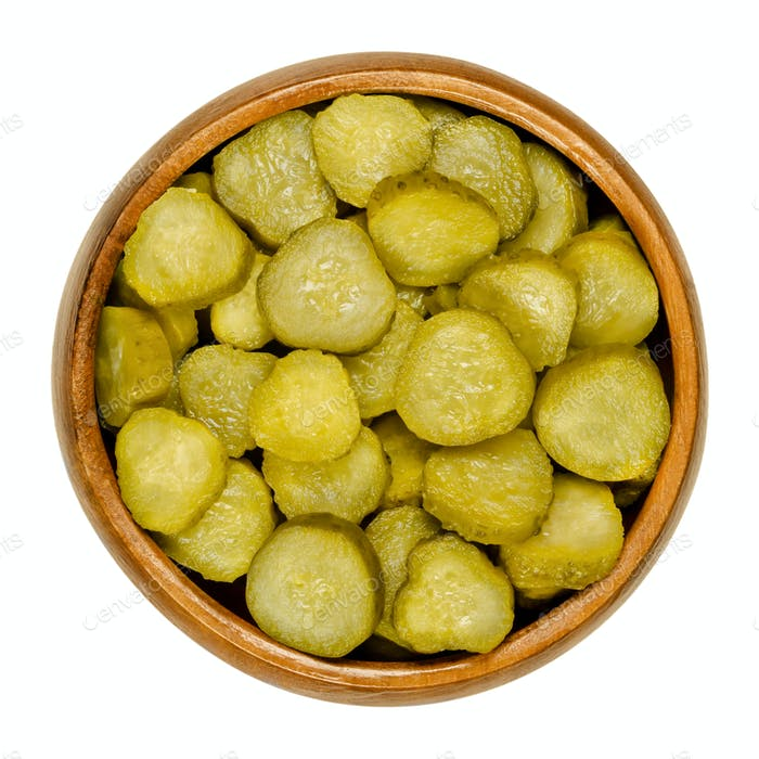 Pickled cucumber discs, known as pickle or gherkin, in wooden bowl