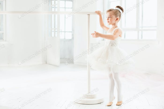 Little ballerina girl in a tutu. Adorable child dancing classical ballet in a white studio.
