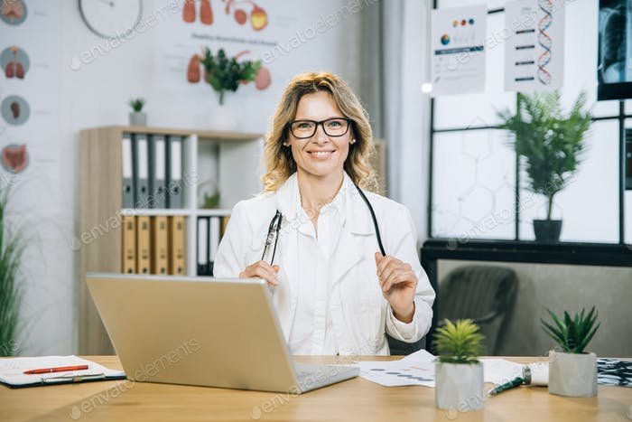 Female physician sitting at desk with wireless laptop