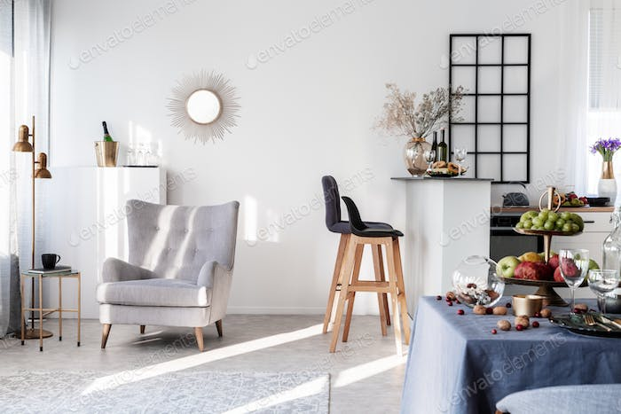 Grey armchair next to two black wooden bar stools