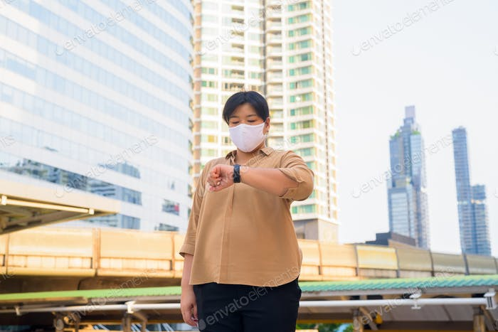 Overweight Asian woman with mask checking the time at skywalk bridge