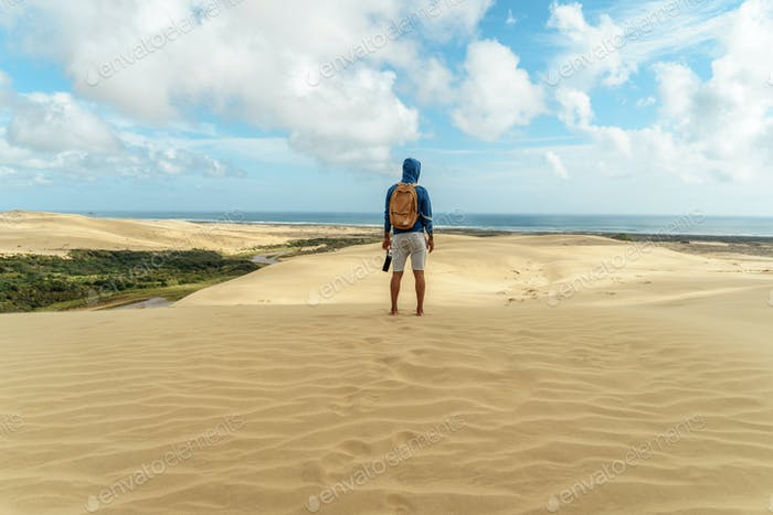 rear view of lonely hiker standing on sand dune and looking away, Giant Sand Dunes, New Zealand