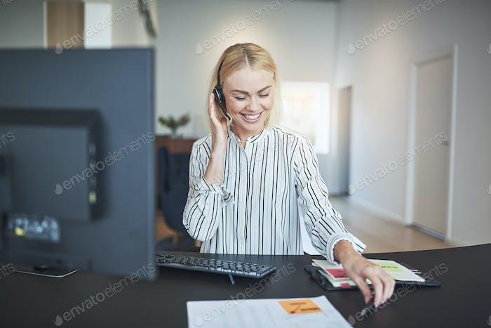 Smiling businesswoman talking on a headset at her office desk