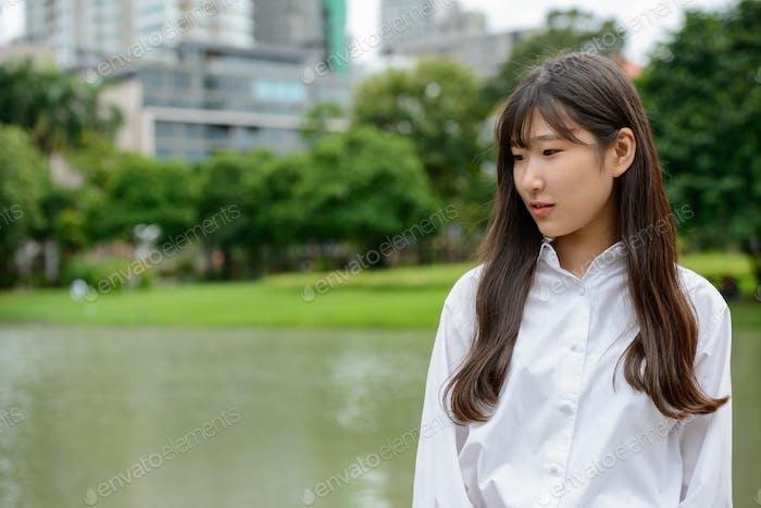 Young beautiful Asian teenage girl thinking at the park