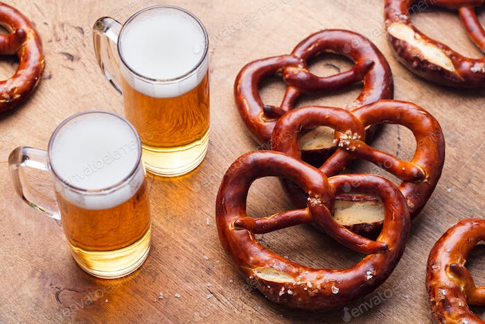 Beer and Salted Pretzels on Wooden Table Background. Close up.