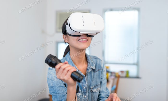 Woman play game with virtual reality device and joystick