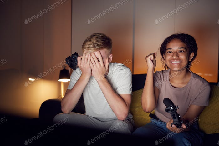 Teenage Girl Beating Boy As They Sit On Sofa At Home Playing Computer Game