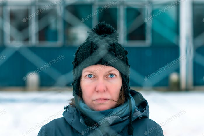 Worried concerned serious woman behind chain-link fence