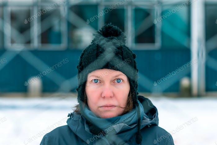 Besorgt besorgt ernsthafte Frau hinter Kettenglied Zaun