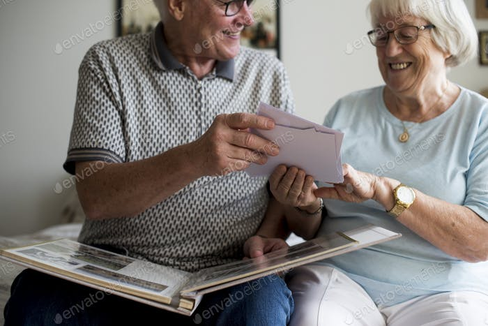 Senior couple looking at family photo album