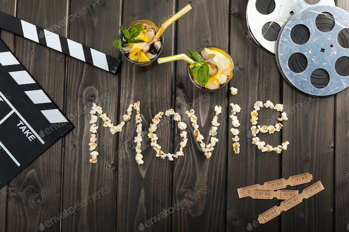 top view of clapper board, drinks, tickets and movie lettering on table, Movie time concept