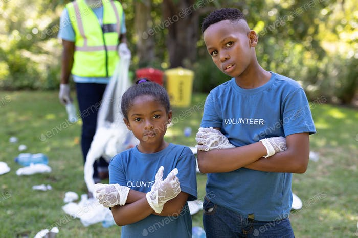 Portrait of a mixed race boy and girl collecting garbage