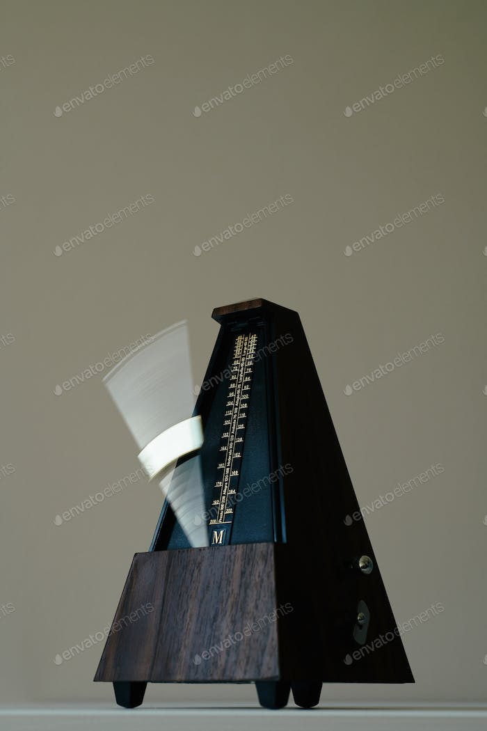 Vintage metronome, on a black background.