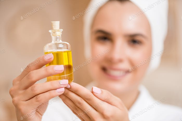 selective focus of woman holding little bottle with massage body oil