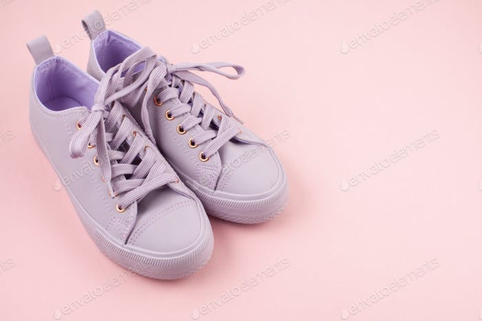 Fashion blog or magazine concept. Pink female sneakers over pastel pink background. Flat lay, top