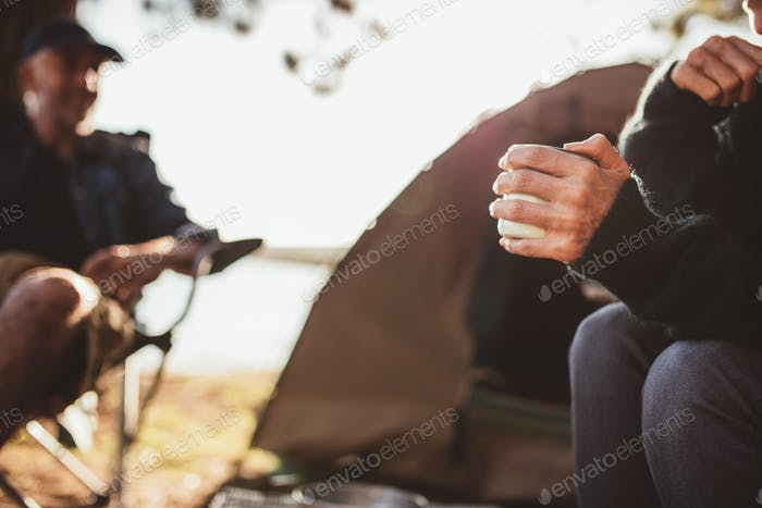 Hand of a woman holding coffee at campsite