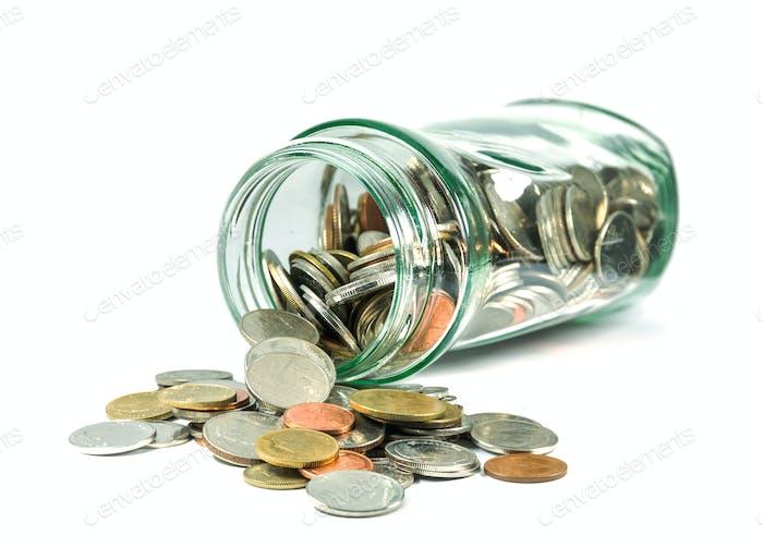 Monedas que se derraman de una botella de vidrio