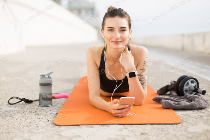 Young beautiful smiling woman in sporty top and leggings with ea