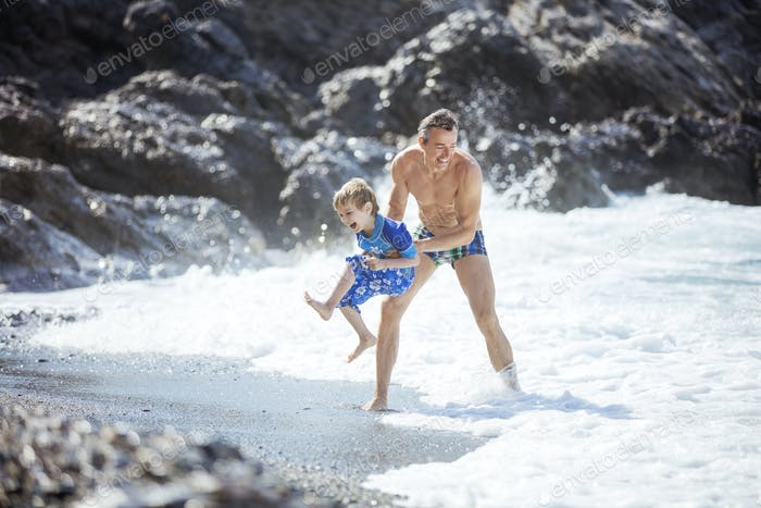 Father and son playing on the beach on summer vacations