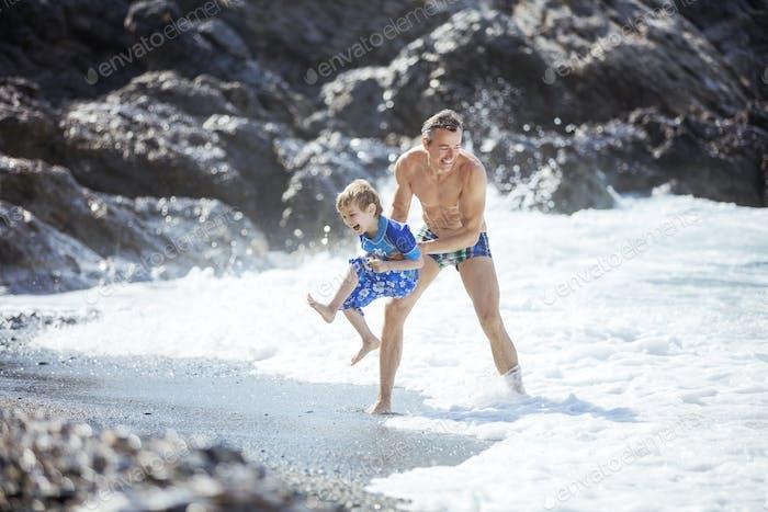 Vater und Sohn spielen am Strand in Sommerferien