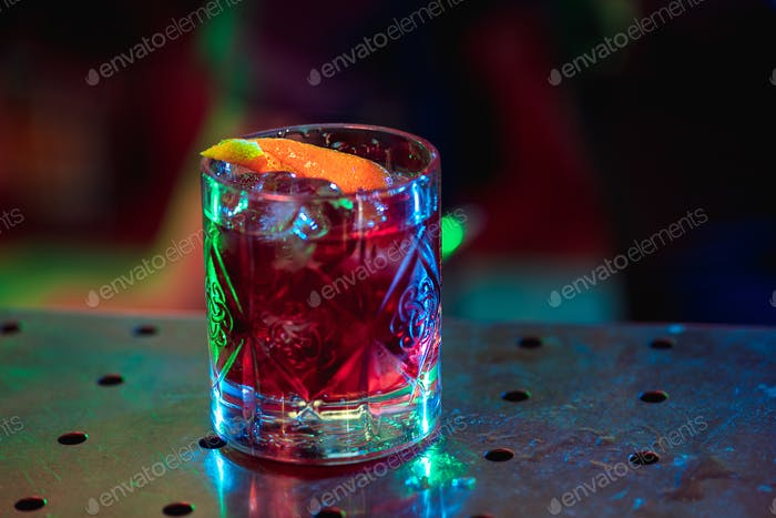 Close up of alcoholic cocktail, beverage, drink in multicolored neon light