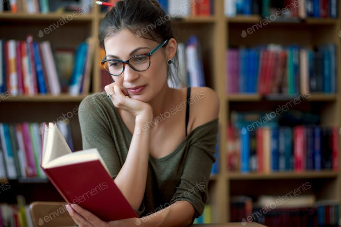 Young smiling woman in glasses reading a book