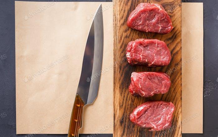 Rohes Rindfleischfilet Mignon Steaks auf Holzbrett und Bastelpapper