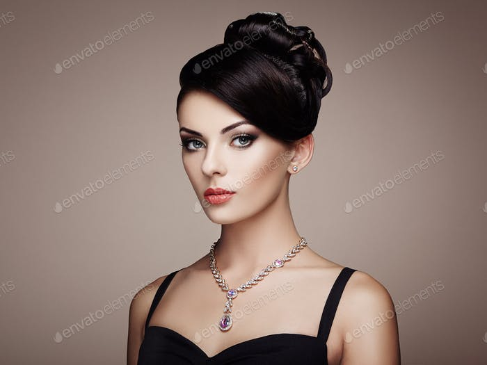 Fashion portrait of young beautiful woman with elegant hairstyle
